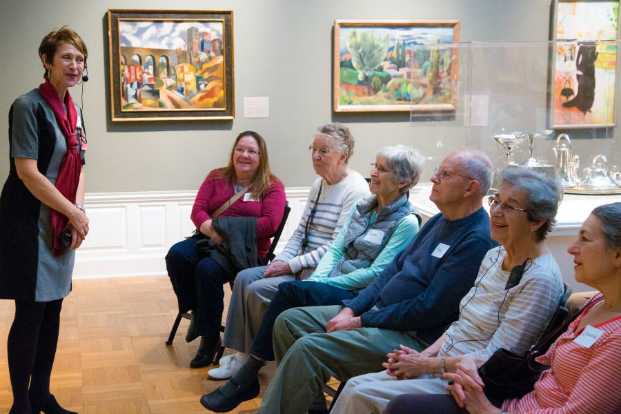 A group of visitors sitting and listening to a docent talk about artwork.