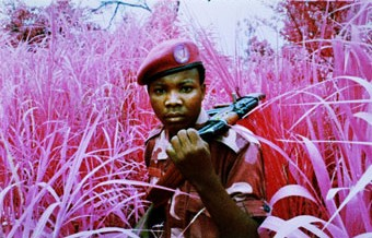 Film still from The Enclave, 2012-2013, showing a rebel from Mai Mai Yakutumba posing in Elephant Grass in Fizi, South Kivu, eastern Democratic Republic of Congo, 16 mm infrared film transferred to HD video, 39 minutes 25 seconds, Produced in eastern Democratic Republic of Congo, Director/Producer: Richard Mosse, Cinematographer/Editor: Trevor Tweeten, Composer/Sound Designer: Ben Frost, Courtesy of the artist and Jack Shainman Gallery, New York.