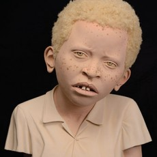 Tip Toland, African Child with Albinism, 2013, paint, pastel, and synthetic hair on clay.