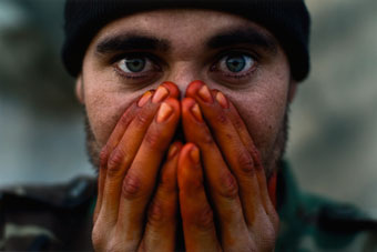 Louie Palu, Afghan Soldier Warming His Henna-Stained Hands on the Front Lines, Zhari District, Kandahar, Afghanistan, 2007, pigment print, Portland Art Museum: The Blue Sky Gallery Collection, gift of the artist.