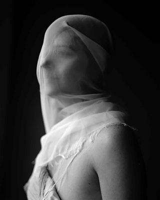Photograph of woman under a veil.