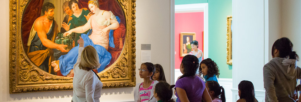 Docent discusses a painting with a school tour group