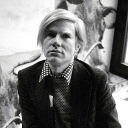 Andy Warhol sitting during the opening of his exhibition at the Whitney Museum