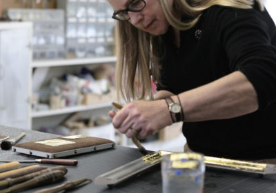 Photo of Nancy Thorn applying gilding to frame
