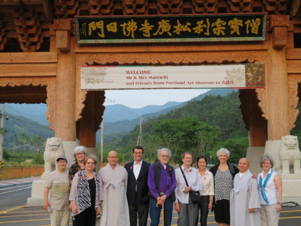 "At the entrance to Songgwangsa, Venerable Il-hwa (third from left), Director of General Affairs for Songgwangsa, and Venerable In-seok (second from right) welcome the Portland group. A banner reading ""Welcome Mr. & Mrs Mattielli and Friends from the Portland Art Museum"" graces a newly build gateway. June 22, 2017."