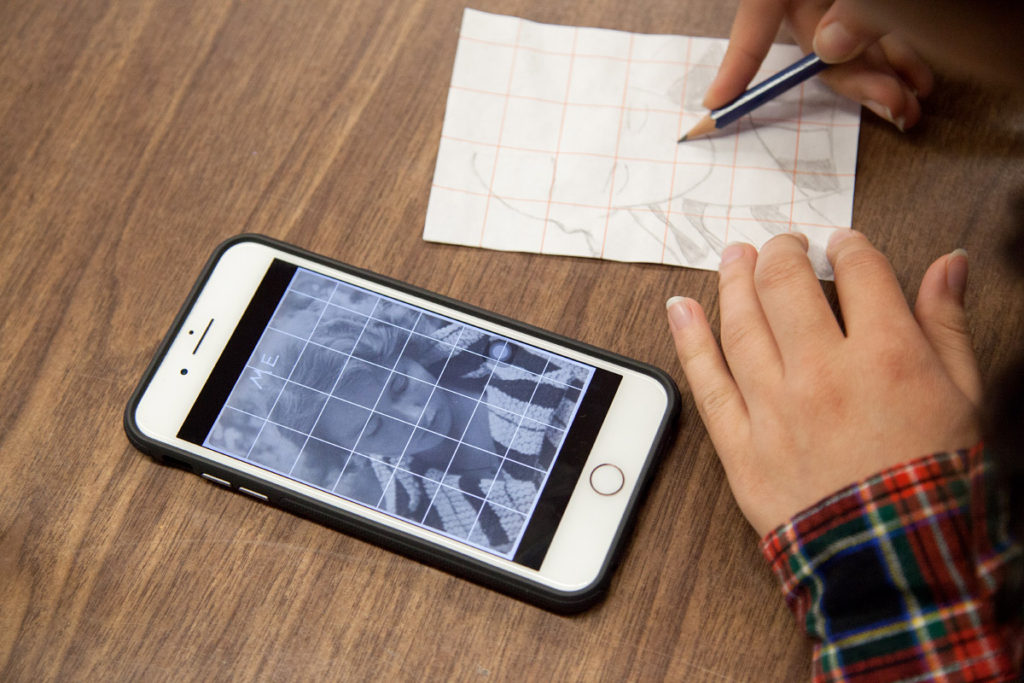A student reproducing a mobile phone photograph with graphite on paper.