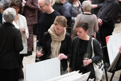 Print Fair attendees looking at prints and conversing.
