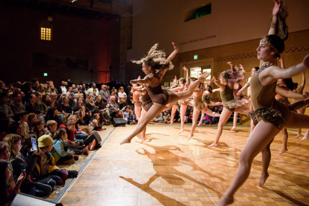 Dancers on stage performing for an audience.