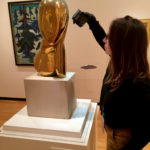 Karen using a handheld light to conduct a preliminary examination of A Muse while still in the galleries.