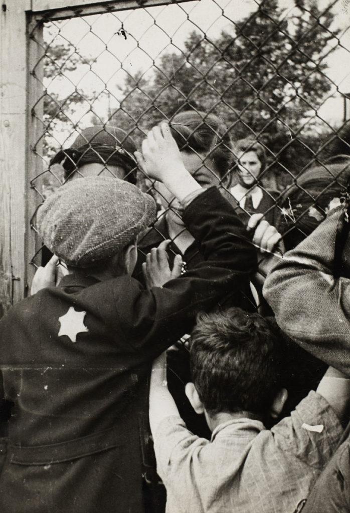 Henryk Ross, Children talking through fence of central prison on Czarnecki Street prior to deportation, 1940-1942