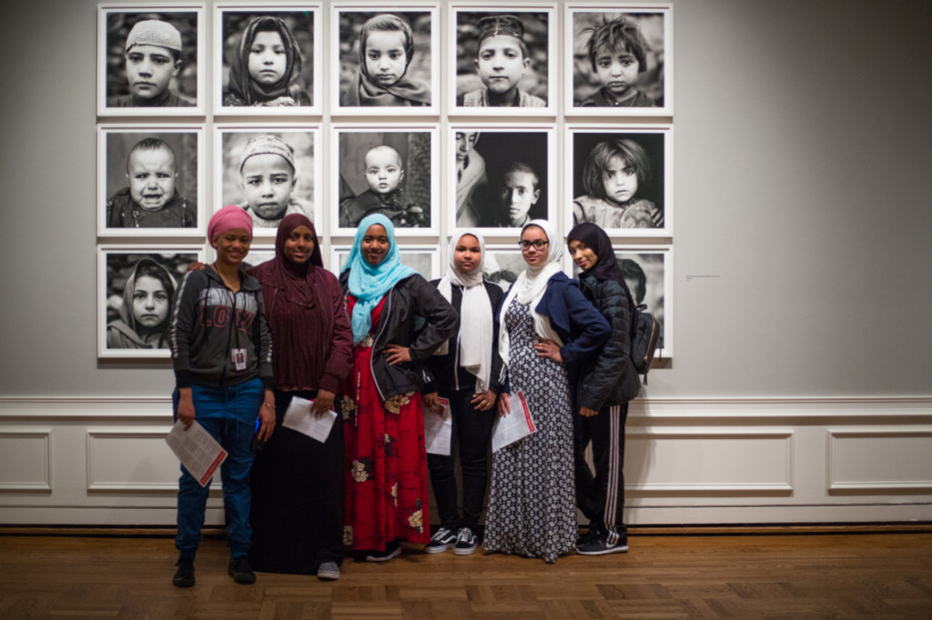 Museum visitors posing in front of photography installation