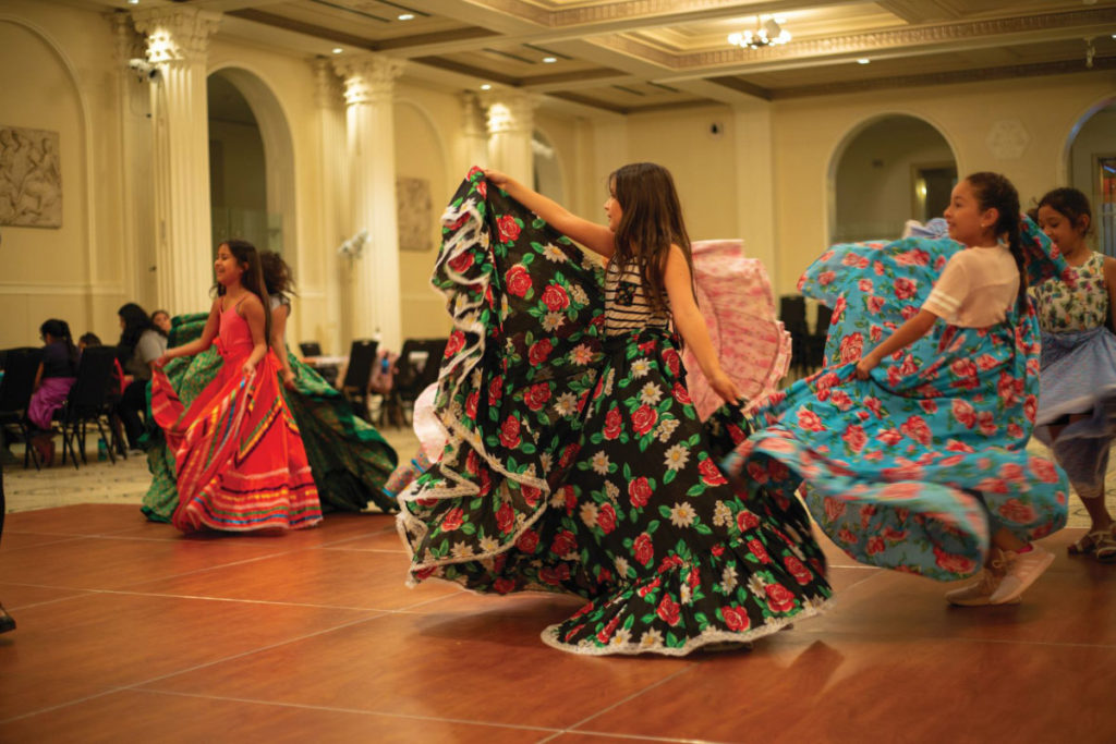 Latina youth performing folkloric dancing.