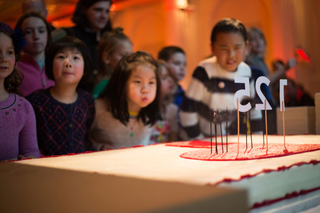 Children blowing out candles on 125th Anniversary cake.