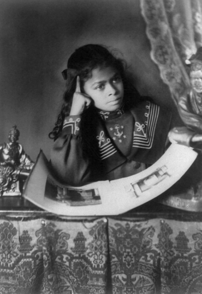 Thomas Askew, African American girl, half-length portrait, with right hand to cheek, with illustrated book on table (1899 or 1900)