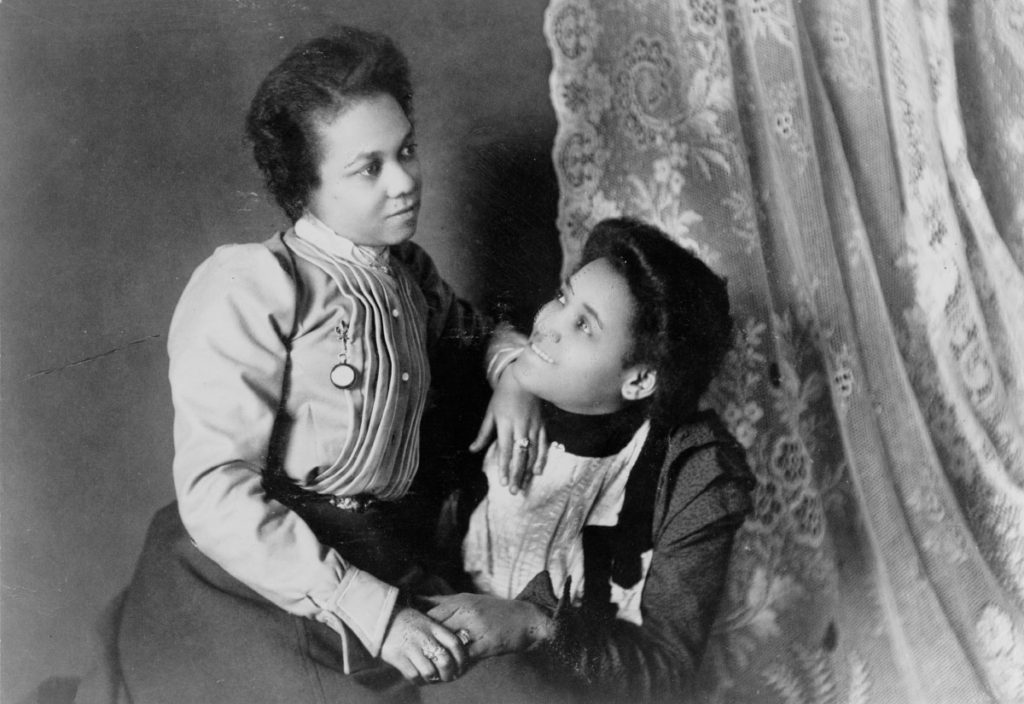 Two African American women, three-quarter length portrait, seated, facing each other (1899 or 1900)