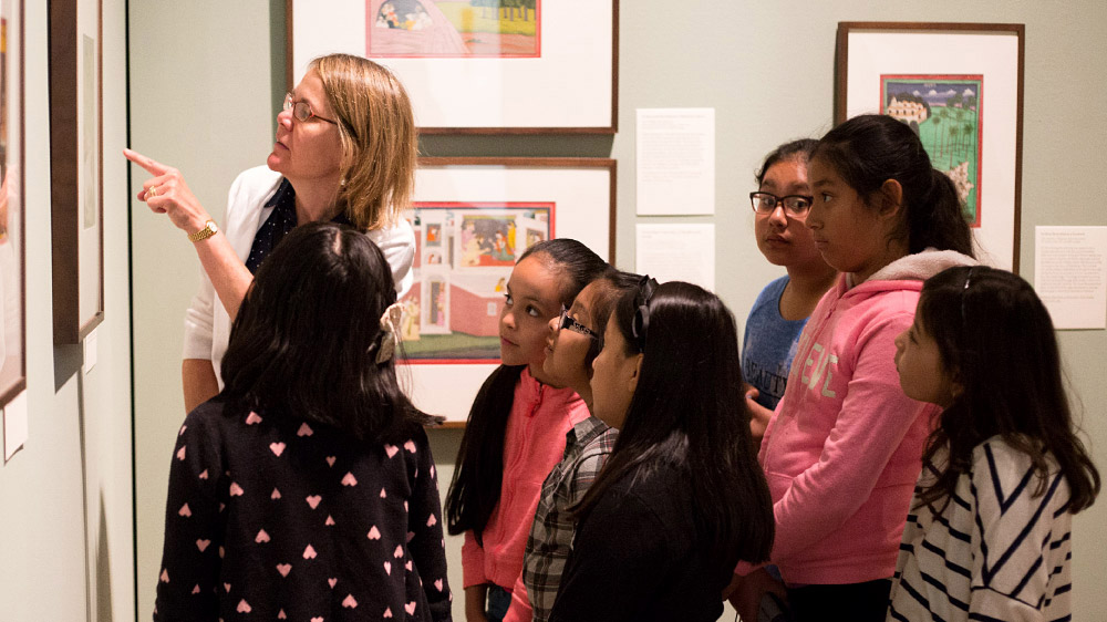 Docent giving a tour to a group of children.