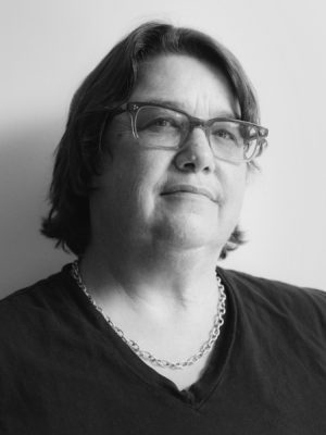 Black and White portrait of Catherine Opie, who has chin-lengh dark hair and is wearing glasses and a necklace